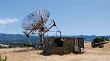 A small shack out on a hill. Standing next to it is a large satellite dish pointed outwards.