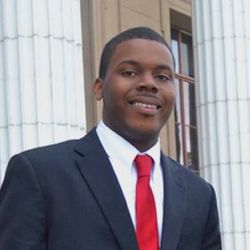 Michael Tubbs wearing a suit with a red tie.