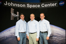 Hopkins, Kotov, and Ryazanskiy stand together in front of a large picture of the Earth and a space shuttle. The picture is labeled 'Johnson Space Center.'