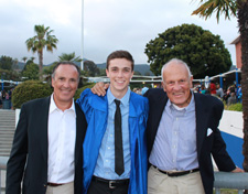 Mack, his father, and his grandfather stand together on campus. Mack is wearing a blue graduation robe.