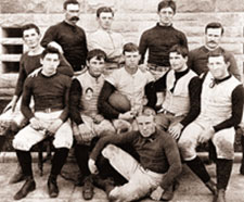 Stanford's pioneer football team. The men are dressed in tight black shirt and white pants, sporting long black socks and shoes.