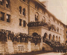 A photo of Encina hall with people tightly packed out front, on the stairs, and on the balcony.