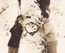 David and Allene together, before Allene's death. They stand on opposite sides of a pine tree, with a heart with an arrow through it drawn over the snowy branches.