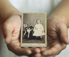 A photo of two hands cupping a black-and-white photo of Leland Stanford as a young boy.