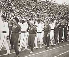 US and Soviet athletes marching side-by-side. One side wears dark uniforms labeled CCCP, the other wears white.