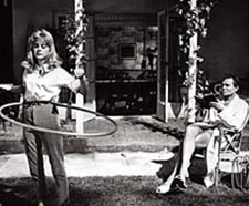 A man in a white suit is seen holding what appears to be a book. In front of him is a young woman in pants and a button down twirling a hula hoop.