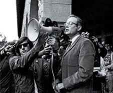 Richard Lyman is speaking through a megaphone a younger man is holding up to his face. He is surrounded by a crowd of people, some of whom hold cameras.