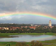 A photo of Lake Lagunita, filled up with water, with a rainbow overhead. Behind the scene, one can see the tops of campus buildings.