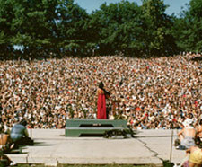 The Grateful Dead stand on the stage of Frost Amphitheater on a bright, sunny day. The crowd is very densely packed, covering the entire lawn.