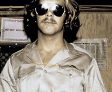 A guard from the Stanford Prison experiment. He wears black aviators and a silky button-down shirt.