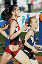 Alicia Follmarr is seen running on the track with blood streaming down her forehead. She sprints alongside another runner.
