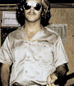 A guard from the Stanford prison experiment. He wears dark aviators and a silky button-down shirt.