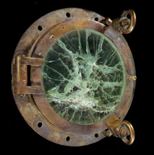 A porthole from the Lusitania. The metal surrounding the window is deeply rusted. The window itself is a faded green and is covered in thick cracks.