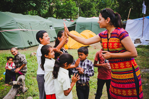 A female volunteer worker high fives a boy over a group of young children. They are all well-dressed or in what appear to be school uniforms. To the left, a man sits on a log with a younger girl in his lap. Behind them are a series of tents.