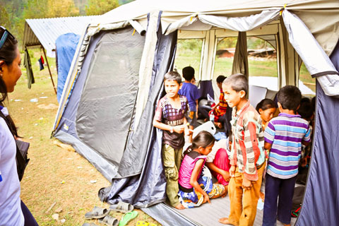 Children are gathered inside a large-tent. Many are sitting in a circle, while others are at the door, looking to an adult volunteer.