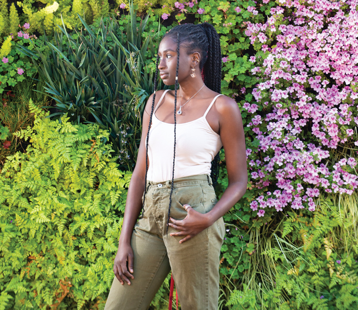 Photo of Esther Abisola Omole in front of flowers and greenery