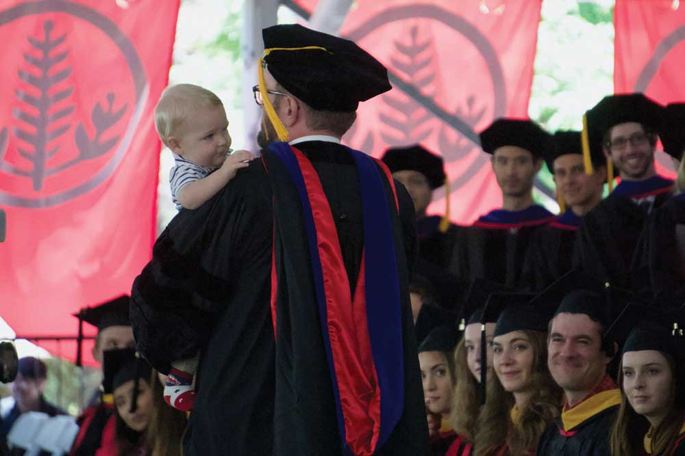 Photo of graduate student crossing the stage with infant.