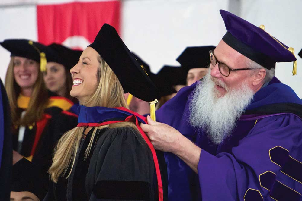 Photo of graduate student receiving her hood.