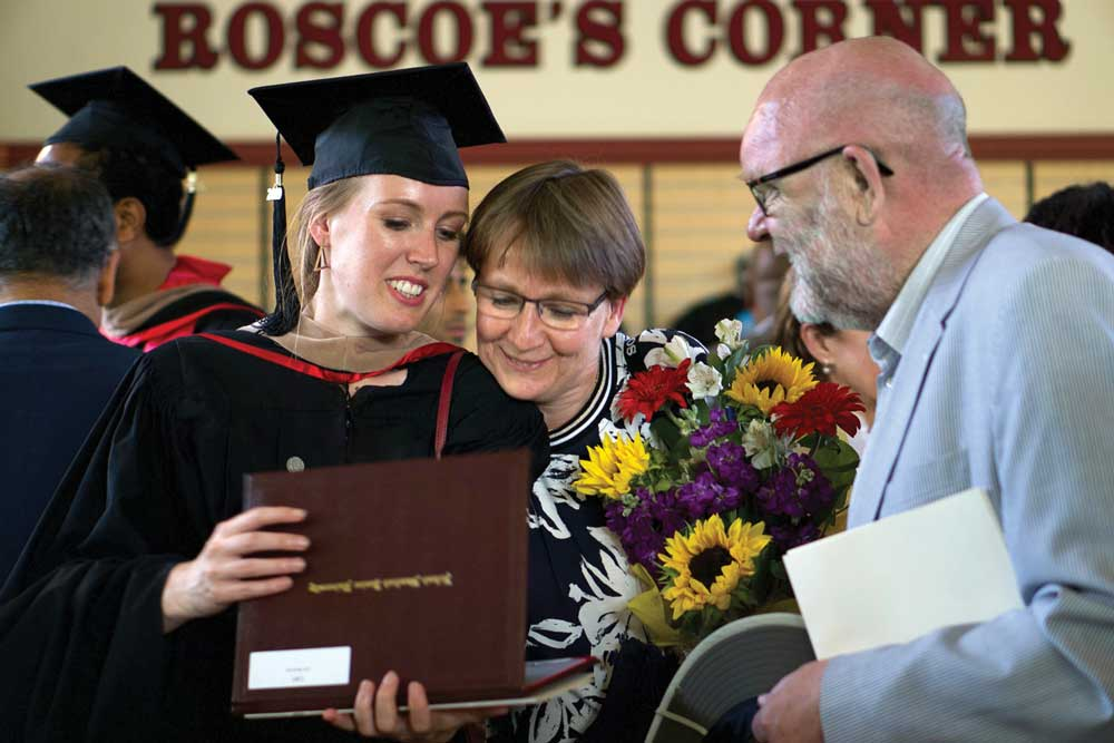 Photo of graduate and family members looking at her diploma.