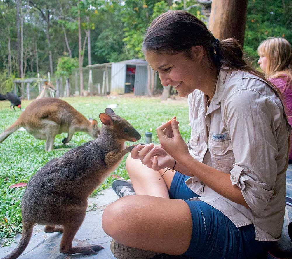 "Stephanie Sila, '19 (right), feeds Hobbsy, a pademelon, at Sheoak Ridge Nature Reserve in Far North Queensland in 2017. Hobbsy ""would hop through our midday lecture in search of sweet potatoes and stomach scratches,"" says Christina Styliani Savvides, '19."