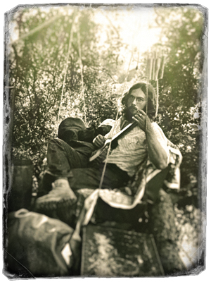 Black and white photo of John Church playing a guitar in his tree house.