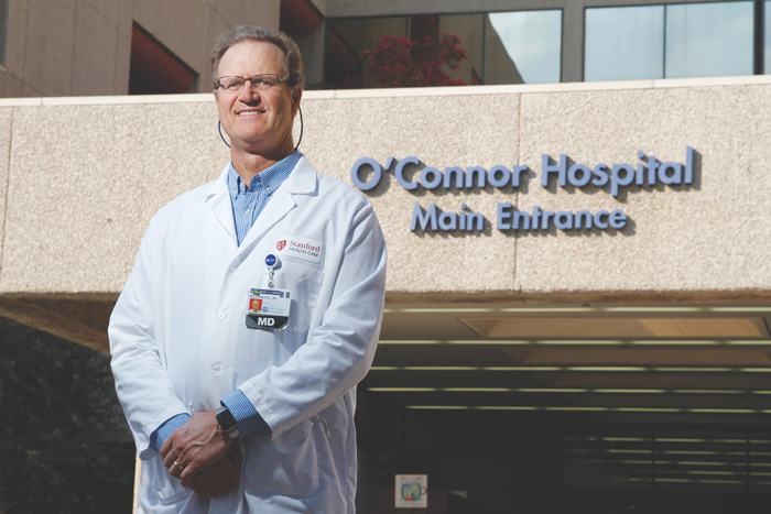 Photo of Milt McColl in his doctor's coat in front of O'Connor Hospital.