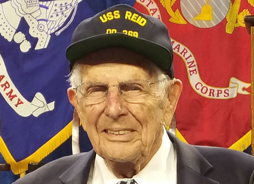 Portrait of Len Gardner, wearing a USS Reid Navy ship baseball hat, smiling in front of military flags.