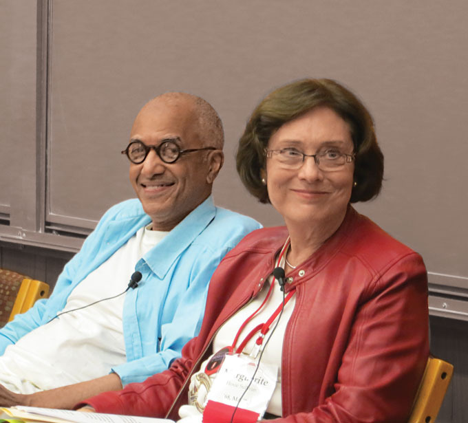 Washington is to Sullivan's right, slightly behind her. Both are wearing white shirts, though Washington has on a blue button down while Sullivans wears a red jacket.