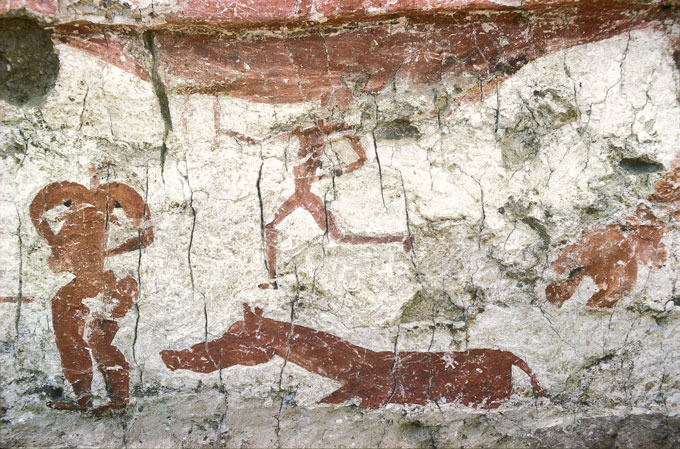 Red, painted figures decorate a thoroughly cracked rock face. On the left is what appears to be a large person. On the bottom is some sort of four-legged create which may be a horse or a pig. Above the creature is a figure that appears to be running.