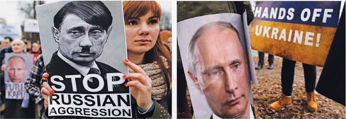 Protestors hold up signs with Putin's face. On the left, a poster shows Putin with the same hairstyle and mustache as Hitler. On the right, a poster reads 'HANDS OFF UKRAINE!'