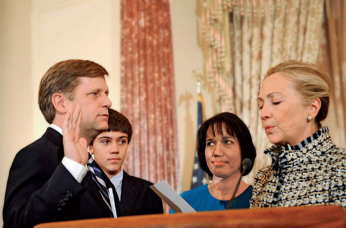 McFaul is standing adjacent to Hillary Clinton with his right hand upheld. Secretary Clinton is looking down at and reading from a piece of paper. Behind the two are Norton, closer to McFaul, and a fourth person who is looking towards McFaul.