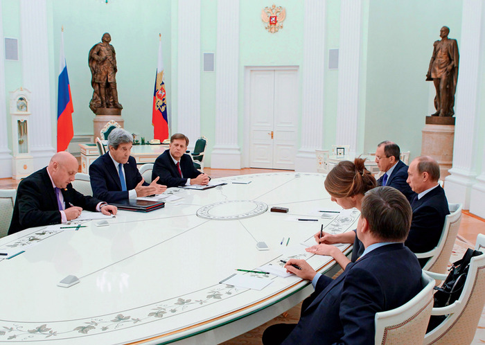 Kerry, McFaul, Putin, and others sit around a decorative table in a large, teal-colored room. Kerry and McFaul sit across from Putin, and Kerry is the one talking. In the background, there are two large bronze statues and a Russian Flag.