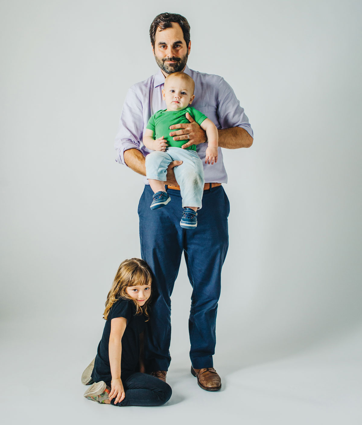 Frank standing against a white background with his two kids, Jonah and Madeline