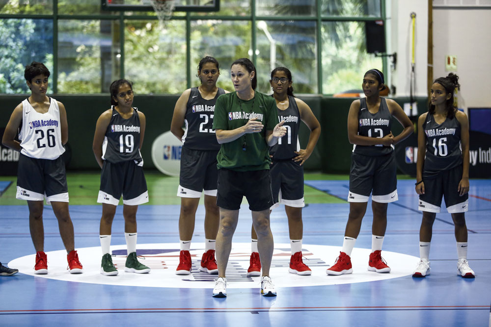 Jennifer Azzi, technical director of the NBA Academy Women's Program, teaching her students on a basketball court.