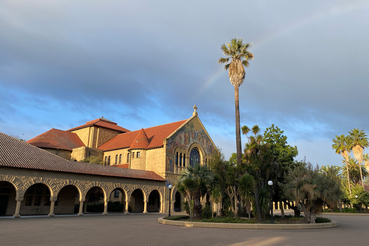 Empty Stanford quad with rainbow arching behind a palm tree.