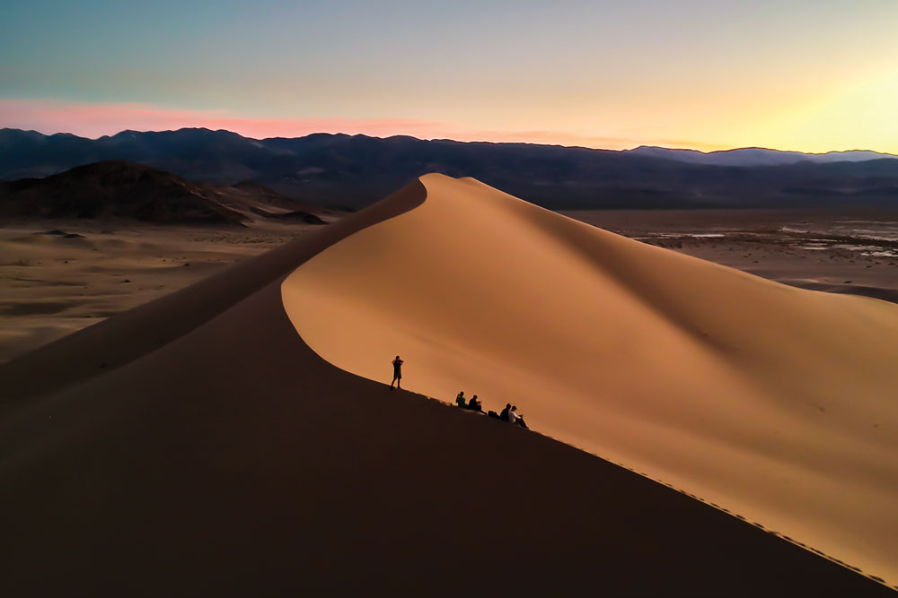 Students standing on top of a sand dune in at sunset.