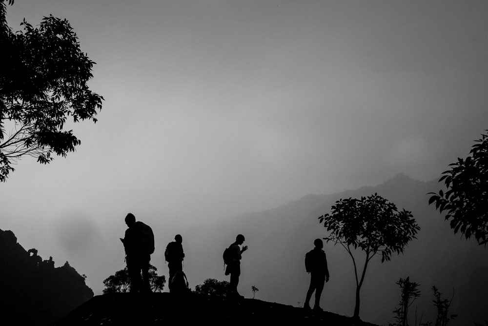 Black and white photo of students hiking through a rain forest in Hawaii with mist and trees.