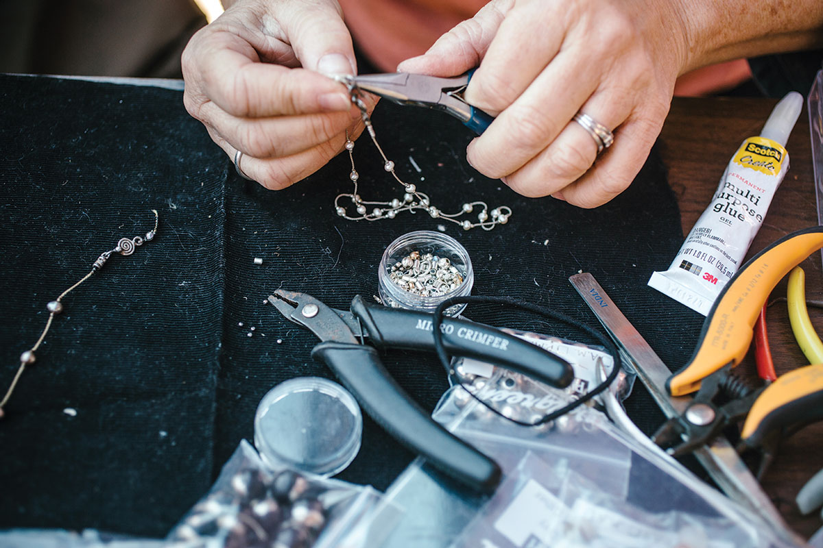 Close-up photograph of hands fixing a metal beaded necklace with needle-nosed pliers.