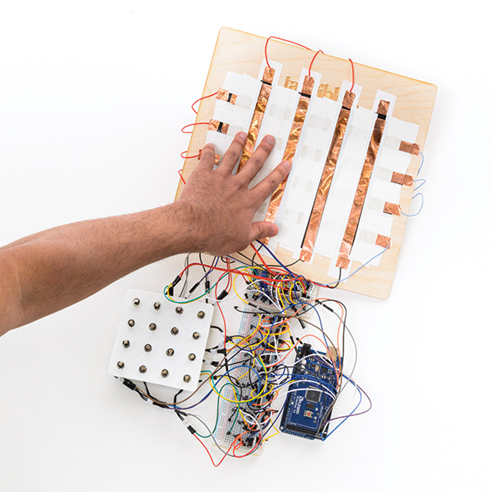 "Close-up photo of Dinakar's invention ""Terrain,"" a wooden board with a grid of copper sheeting and wires connected to three other boards—a circuit board, a wired connectivity board, and a 4x4 grid of metal buttons."
