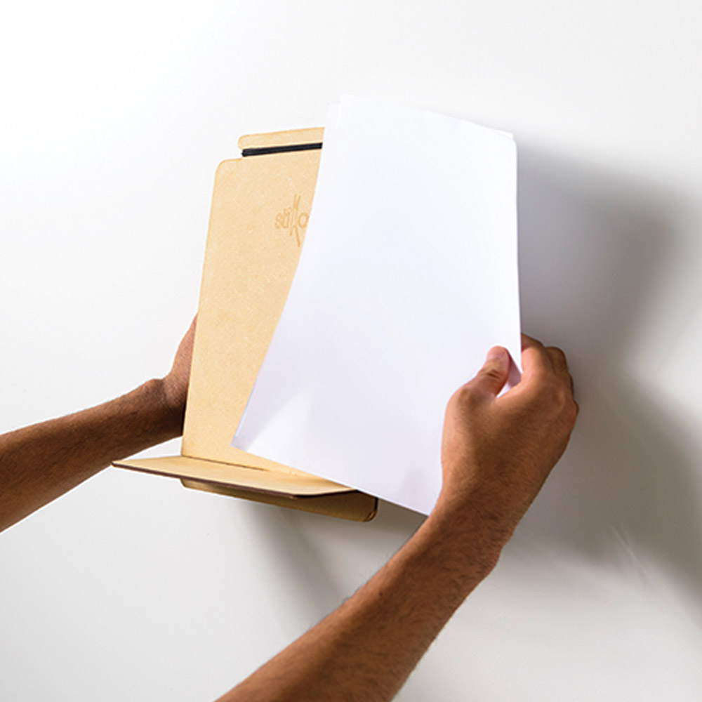 "Close-up photo of Dinakar's invention ""Stikato,"" a golden-colored music stand about the size of a sheet of paper with a small shelf extending out the bottom. A pair of hands demonstrate its size next to a white sheet of paper."
