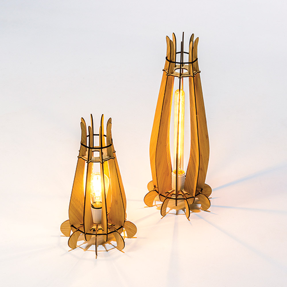Photograph of two Diya lamps designed by Dinakar. They appear to be about a foot tall and resemble the look of lanterns, shaped somewhat like a tulip before it has opened, somewhat like rockets. They are made of 3D printed wood cutouts that are then constructed.
