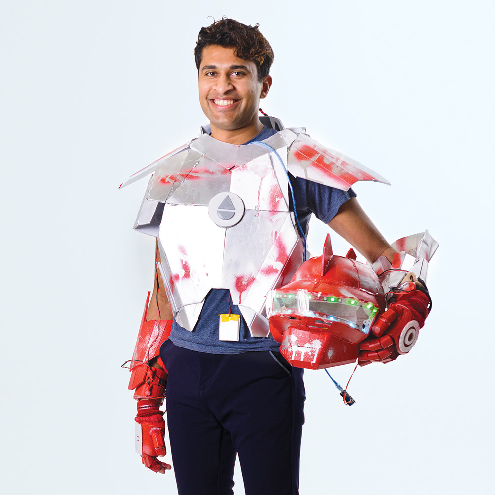 Photo of Akshay Dinakar, class of 2019, wearing his handmade robot suit. It resembles the look of a knight's armor, with scattered red spray paint on an otherwise silver metallic material. The red plastic gloves and armguards are wired and connected to the suit. He holds the helmet under his  left arm, which has blinking colored lights around the visor and red fins coming out of the top.