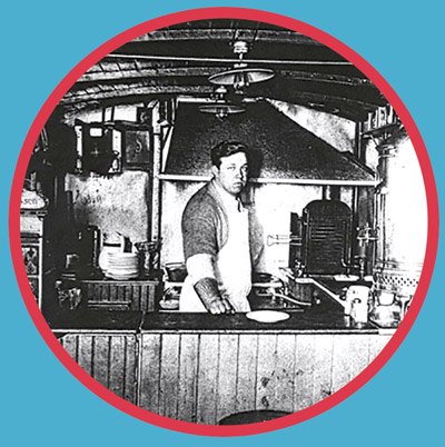 Louis Lassen standing behind restaurant counter wearing an apron.