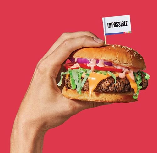 "Hand holding an Impossible Burger with a toothpick flag that reads ""Impossible""."