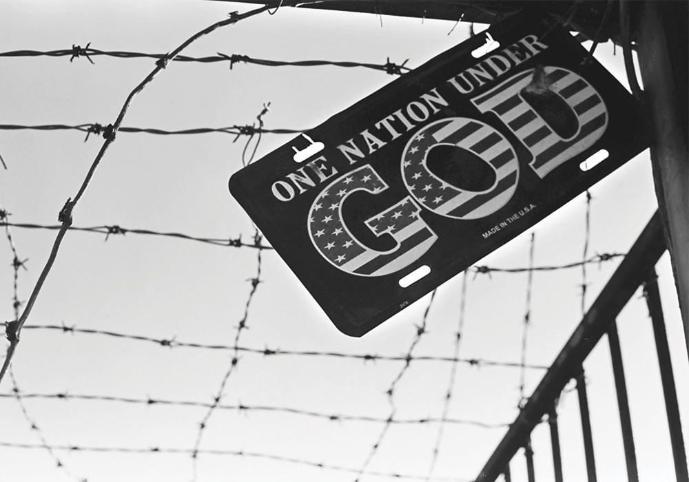 "A metal sign that reads, ""One Nation Under God"", hanging against a barbed wired fence."