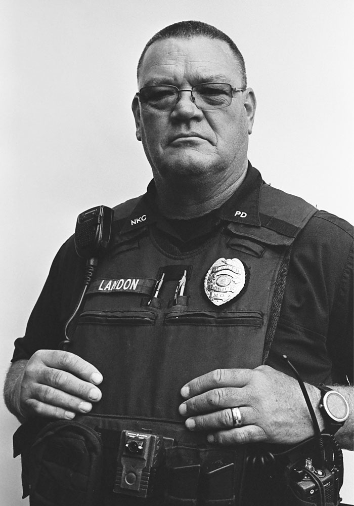 Portrait of a middle-aged police officer in full gear, wearing glasses, and posing.