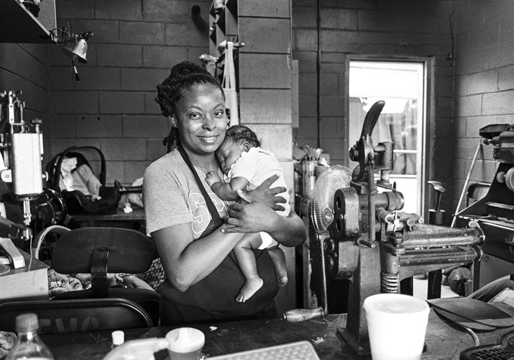 A smiling African Amercian woman in an apron, holding an infant in her work area.