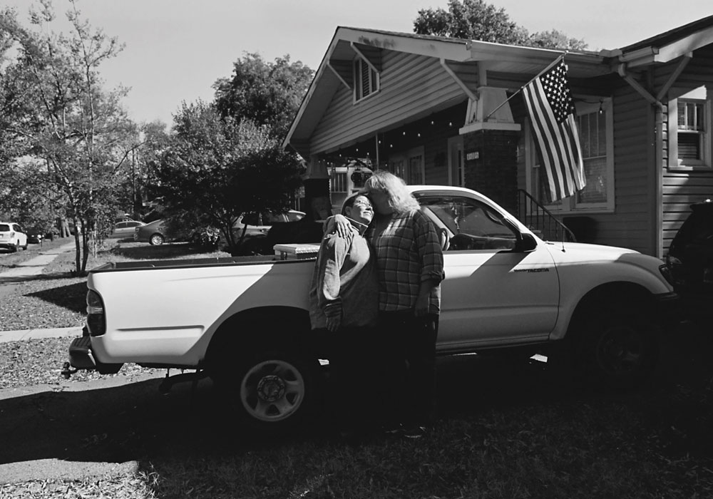 Two individuals embracing in a hug in front of a white truck.
