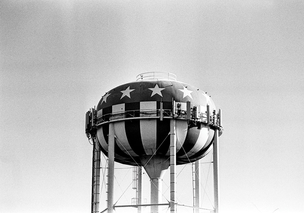 The top of a water tower, painted to look like an American flag.