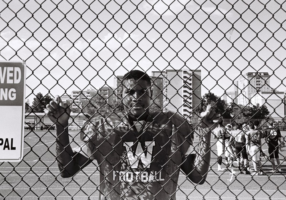A young, African American male in a football uniform, holding on to a fence on a football practice field.